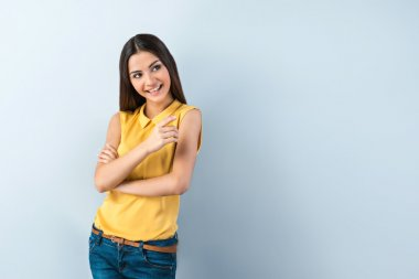 Photo of beautiful young business woman standing near gray background. Smiling woman with yellow shirt looking and pointing aside stock vector