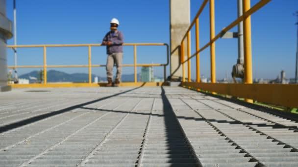 Mann in der Raffinerie-Anlage mit blauer Himmel