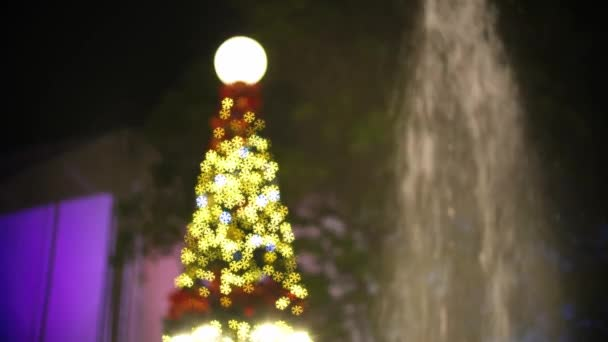 Blurry focus christmas tree in snow bokeh light beside fountain.