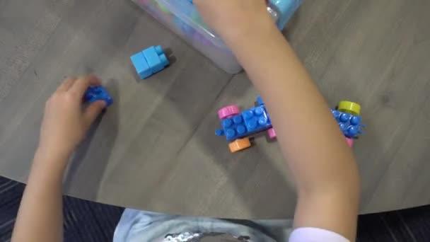 Vysoký úhel pohledu dolů dívka demontovat cihlu a držet zpět kontejner.