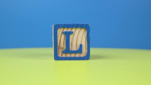 Close up shot letter L alphabet wooden block on surface