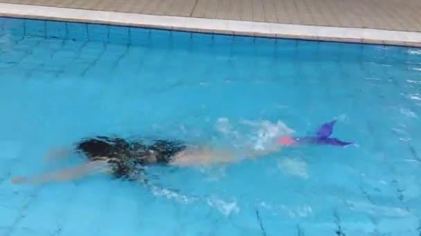 roztomilá dívka s monoploutve plave v bazénu