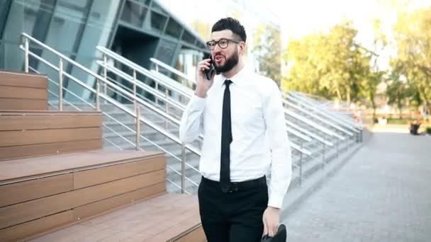 úspěšný podnikatel s vousy mluvit na mobilní telefon venku ve městě