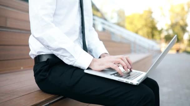 Geschäftsmann tippt im Freien mit Laptop auf Laptop-Tastatur