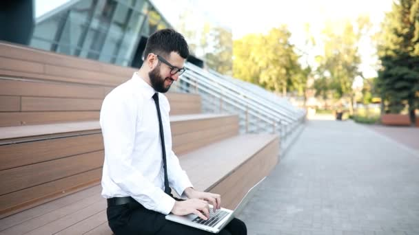 Young businessman in a suit and glasses sitting on the stairs in the city and using a laptop