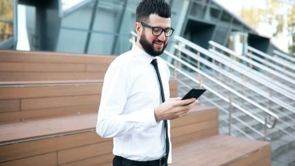 obchodní muž s vousy nosí brýle, oblečený v elegantním oblečení, pomocí mobilního telefonu, mladý podnikatel číst něco na mobilním telefonu během přestávky venku