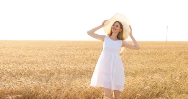 mladá žena v bílých šatech a slaměný klobouk procházející