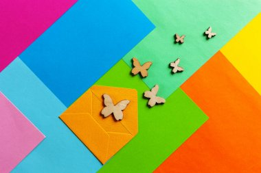 Close up photo of batterflies silhouettes on varicoloured colorful paper background. Top view, spring and various holidays and events concept