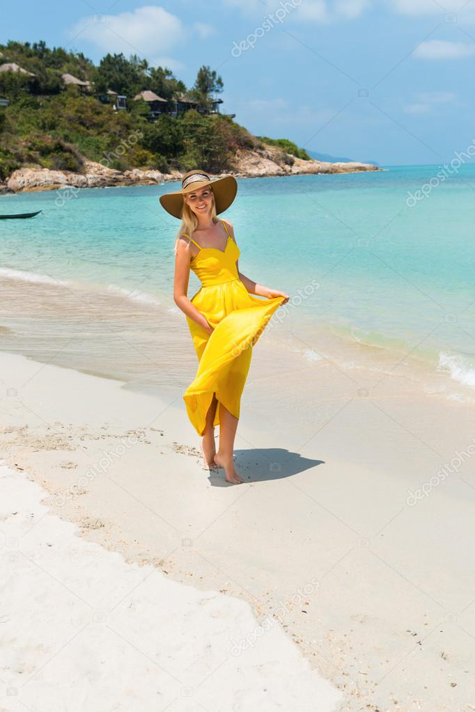 Carefree beautiful fashion blonde female in beach straw hat holding her  long yellow dress and walking barefoot by sand of tropical beach. Natural  woman ... 9fa82f21fb94