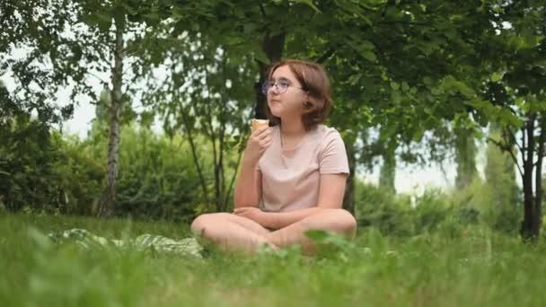 Puberťačka si v létě vychutnává lahodnou zmrzlinu. Dítě se zmrzlinou na procházce v městském parku