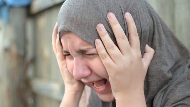 a teenage refugee girl is crying and screaming, holding her head in her hands, screaming in pain.