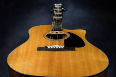 acoustic guitar with yellow deck and black pickguard on isolated black background