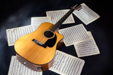 set of sheet music scores and classical acoustic six-string yellow  guitar with black pickguard on isolated black background