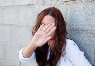 Shy brunette girl covering her face