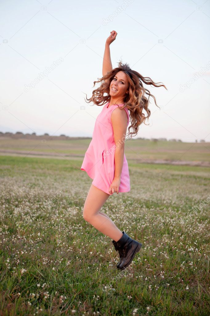 Woman jumping on a flowery meadow