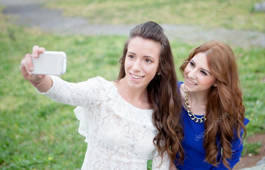 Two girls by becoming a photo with the phone in the park