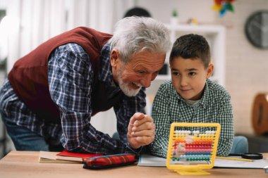 Grandfather and grandson doing homework together. Grandpa and grandson enjoying at home.