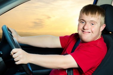 Young man driving vehicle at sunset.