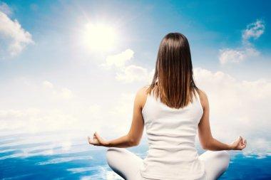 Young woman meditating at lake.