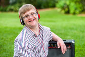 Fotografie Boy with down syndrome wearing headphones.