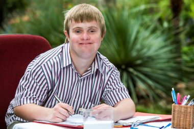 Boy with down syndrome at desk outdoors.