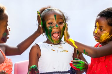 African kids painting friends face.