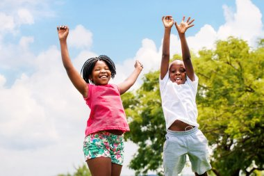 Two African kids jumping in park.