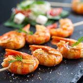Photo Shrimp tails grilled on wood skewer.