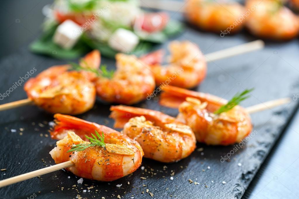 Appetizing grilled prawns on skewer.