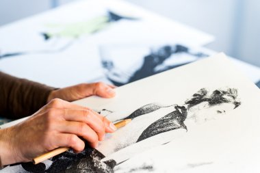 Female hand making fashion sketch