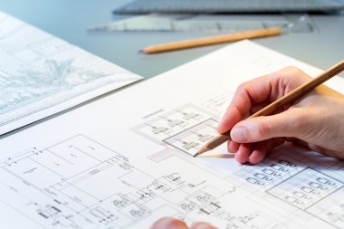 Hand reviewing construction plans.