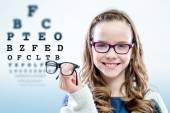 Fotografie Dívka drží brýle s zkušebním diagramu v pozadí