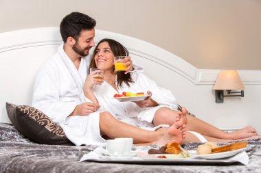 Young couple on honeymoon in hotel room.