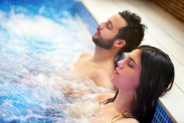 Couple relaxing in spa jacuzzi.