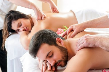 Couple having relaxing body massage in spa.