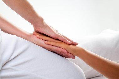 Reiki treatment on girls hand.