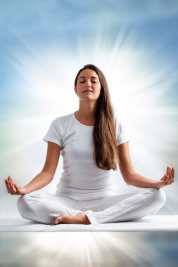 Close up portrait of attractive young woman meditating with eyes closed. Front view of woman dressed in white in yoga position with ray of light in background. stock vector