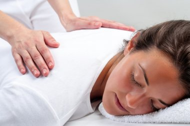 Reiki therapist doing treatment on woman.