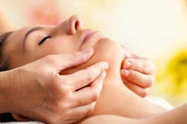 hands massaging female chin