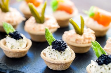 Mini puff pastry tartlets with savory filling.
