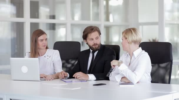 Businessman in suit talking to business people, colleagues or partners sitting at the negotiation table, male leader discussing work at team meeting or group negotiations, talking to clients