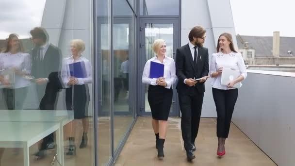 Geschäftsleute, ein Mann und zwei Frauen in Anzügen gehen spazieren und unterhalten sich in der Nähe eines modernen Bürogebäudes, halten einen Computer und Dokumente in den Händen. Diskussion von Kollegen oder Partnern beim Mittagessen