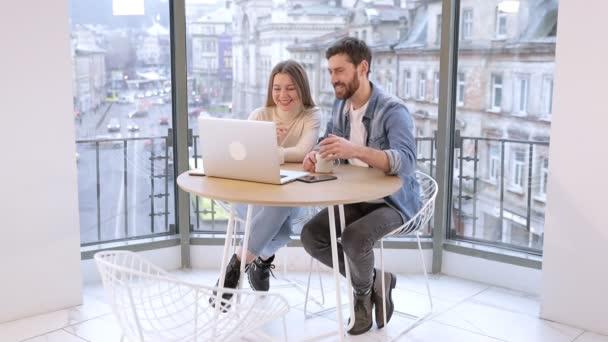 Mladá dívka a muž sedí v kavárně s laptopem, dělají videohovor na webové kameře, mluví během přestávky na kávu.