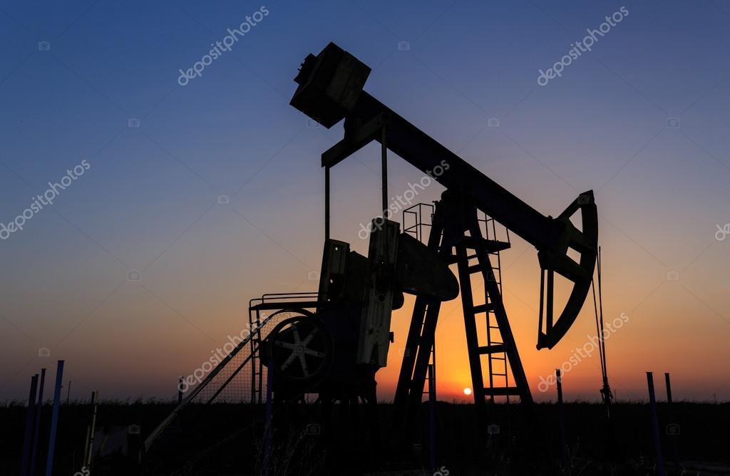 Oil and gas well silhouette in remote rural area