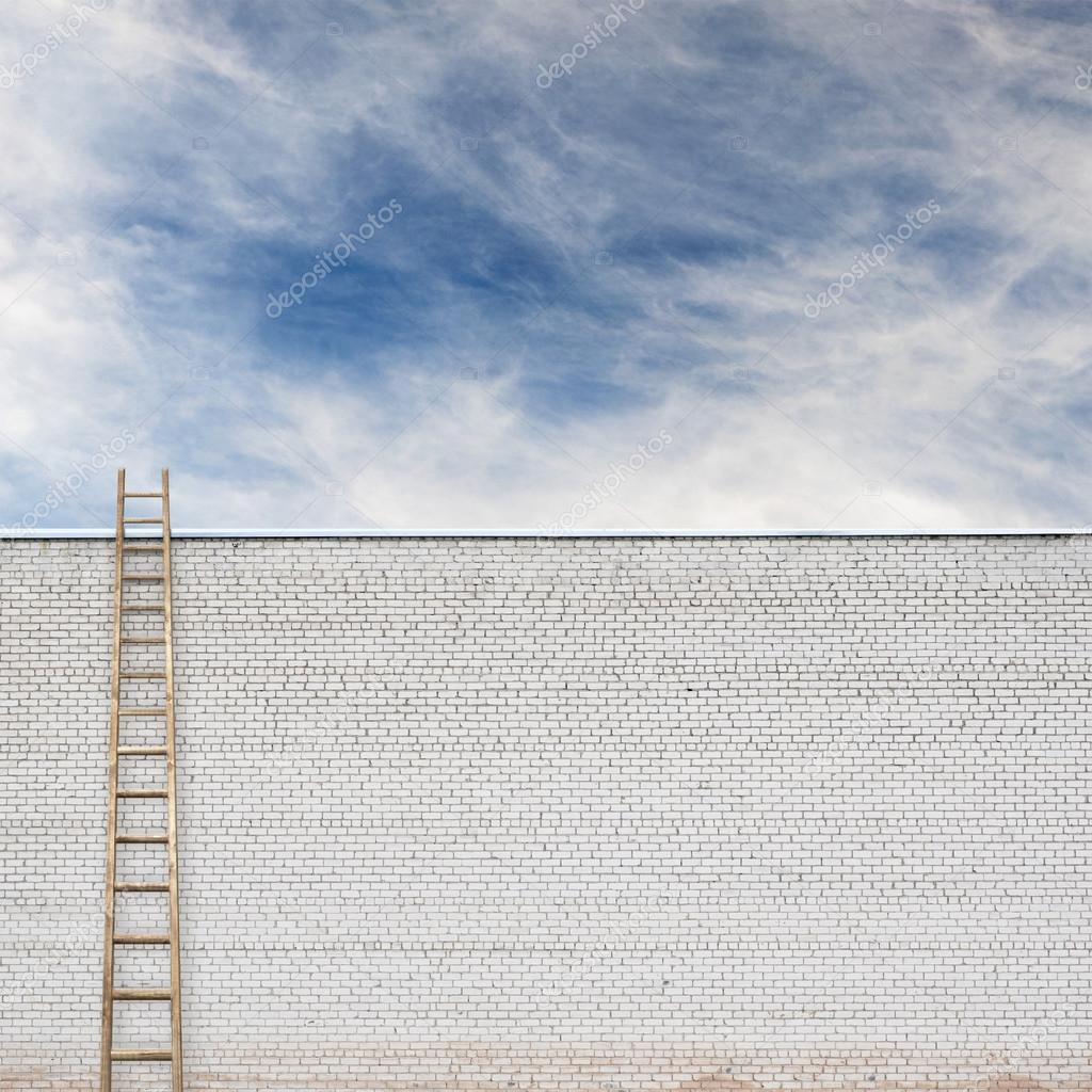 Blue sky behind the huge wall with a wooden ladder