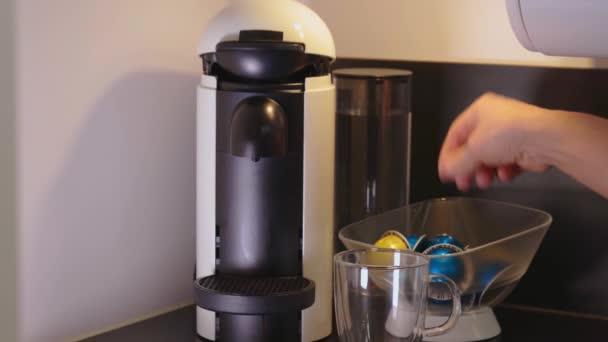 Nahaufnahme der männlichen Hand beladen Kapsel in Kaffeemaschine.