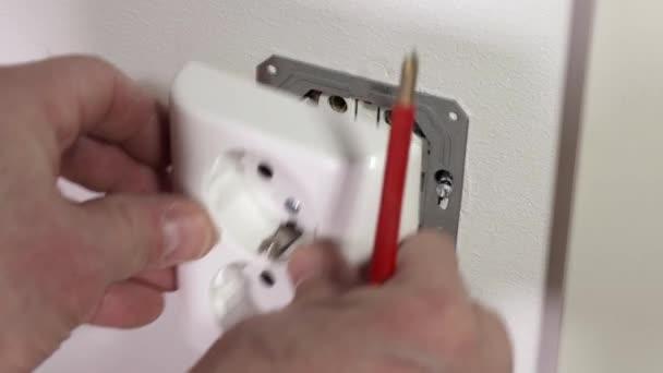 ztratit pohled na elektrikáře, jak opravuje nástěnný vypínač. Koncept stavebních prvků.