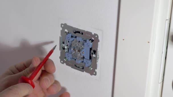 Pohled na muže opravujícího vypínač bílého světla. Koncept elektřiny. Švédsko.