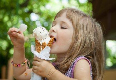 Pretty little girl eating an ice cream