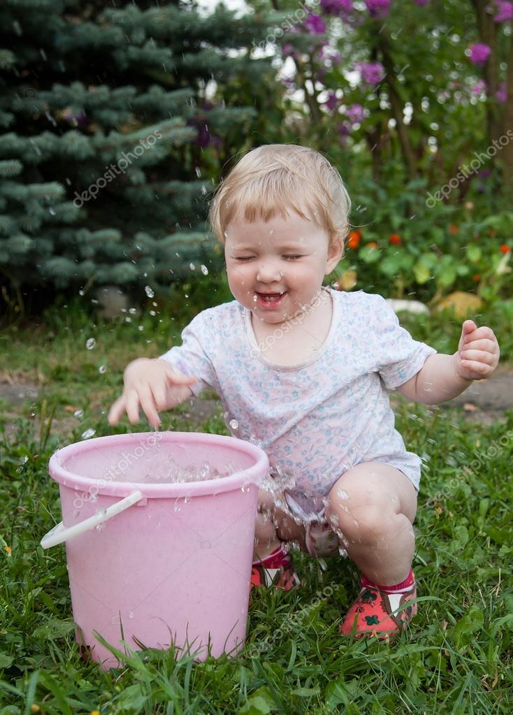 Charming baby girl playing with water